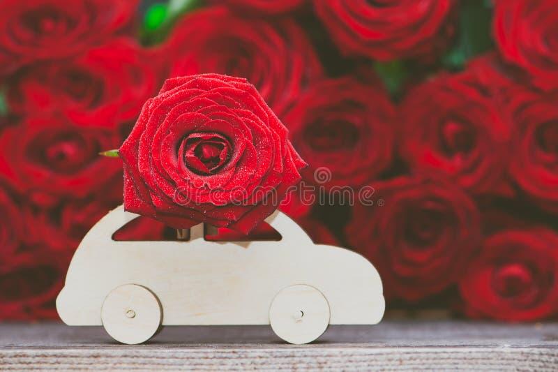 O conceito da entrega da flor, amor, máquina de escrever transporta uma flor contra um fundo do vermelho foto de stock royalty free