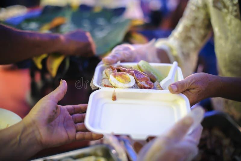 O conceito da esperança: Mão-alimentação ao carente na sociedade: Conceito da alimentação: Os voluntários dão o alimento aos pobr imagem de stock