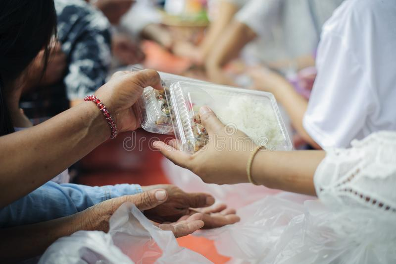 O conceito da esperança: Mão-alimentação ao carente na sociedade: Conceito da alimentação: Os voluntários dão o alimento aos pobr imagem de stock royalty free