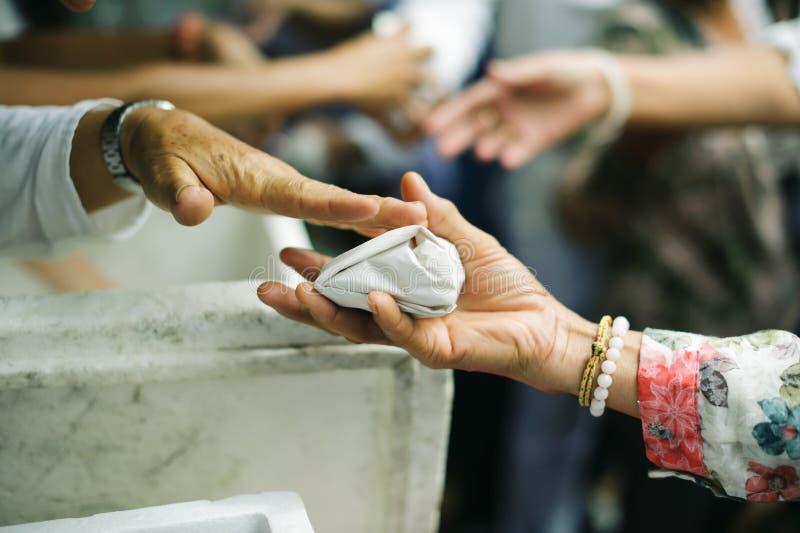 O conceito da esperança: Mão-alimentação ao carente na sociedade: Conceito da alimentação: Os voluntários dão o alimento aos pobr fotos de stock royalty free