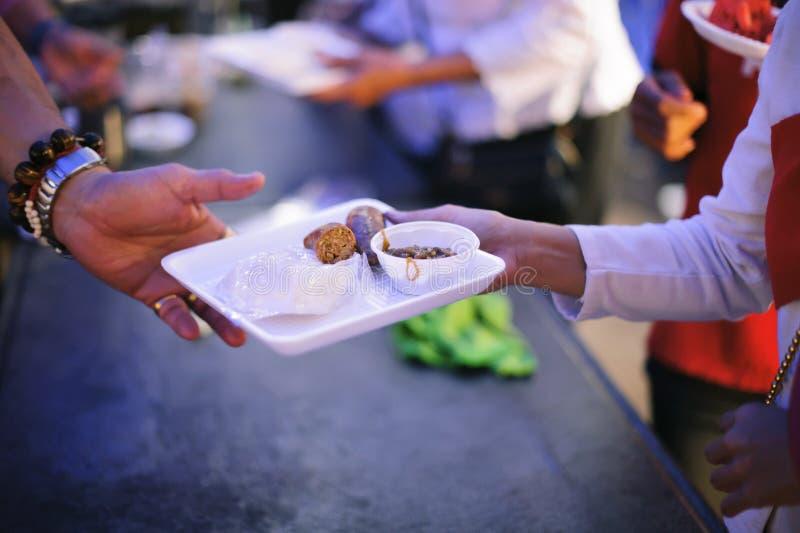 O conceito da esperança: Mão-alimentação ao carente na sociedade: Conceito da alimentação: Os voluntários dão o alimento aos pobr foto de stock royalty free