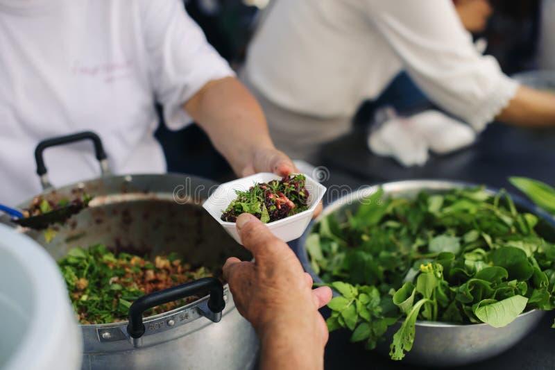 O conceito da esperança: Mão-alimentação ao carente na sociedade: Conceito da alimentação: Os voluntários dão o alimento aos pobr foto de stock