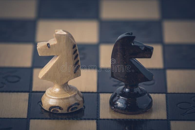 O conceito da estrat?gia da xadrez est? na placa de xadrez imagens de stock royalty free
