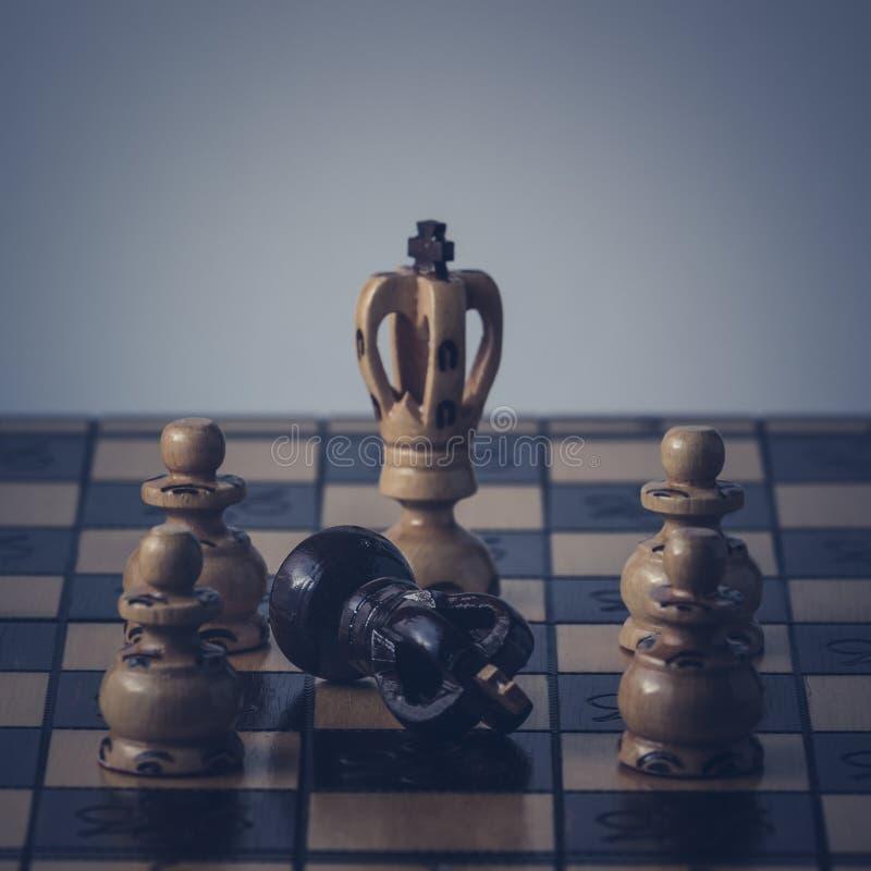 O conceito da estrat?gia da xadrez est? na placa de xadrez fotografia de stock royalty free
