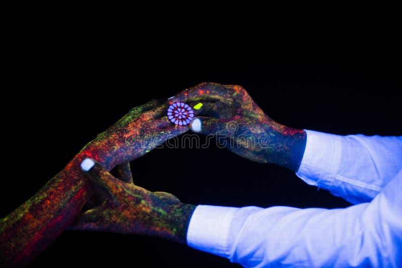 O conceito da fotografia criativa de conexão do casamento das mãos nas palmas masculinas e fêmeas da luz de néon guarda junto em  imagens de stock