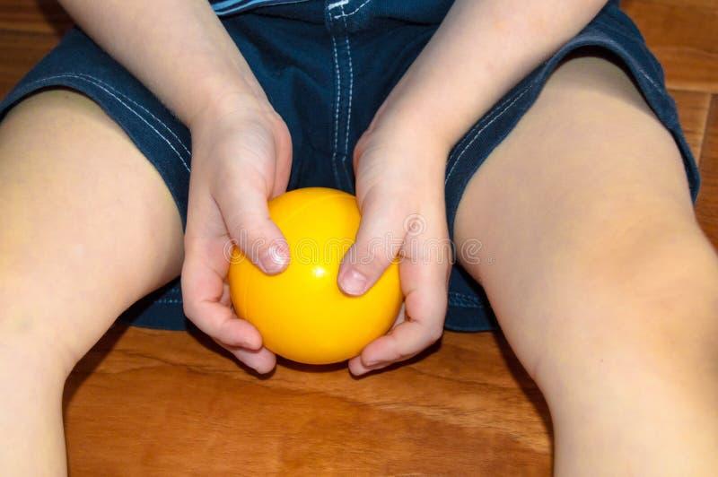 O conceito da infância, PROTEÇÃO da criança - criança caucasiano feliz no short que joga com uma bola amarela no assoalho da casa imagem de stock