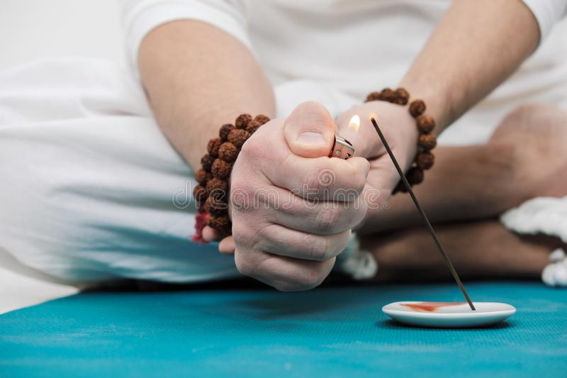 O conceito da ioga e da meditação Close-up das mãos e dos pés de um homem na roupa branca em um fundo claro A foto de stock royalty free