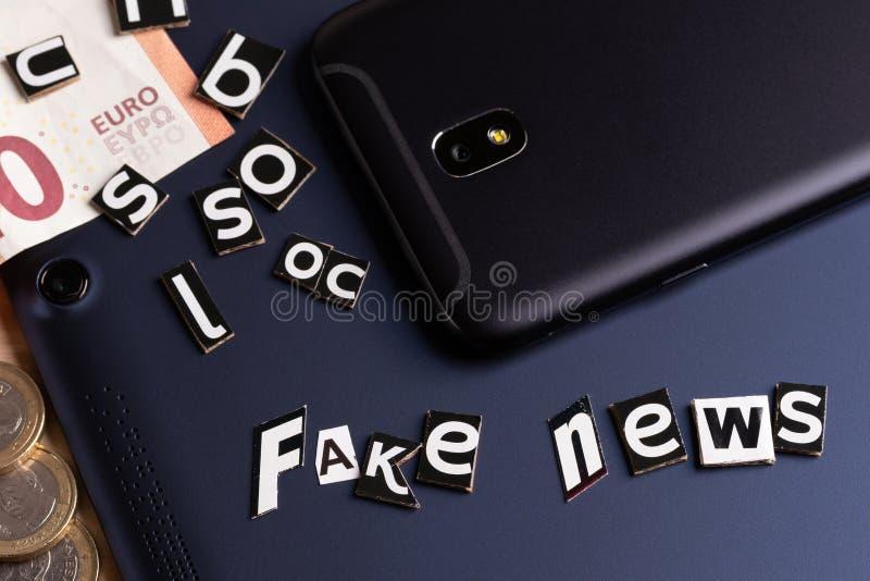O conceito da notícia da mobilidade: tabuleta, telefone do toque, dinheiro e corte do texto com letras fotografia de stock royalty free