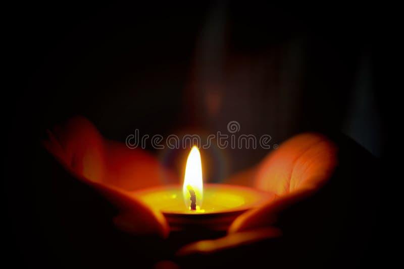 O conceito da oração e da esperança da vela ilumina-se nas mãos fotografia de stock