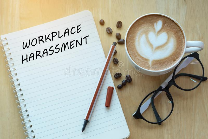 O conceito da perseguição do local de trabalho no caderno com vidros, escreve fotografia de stock
