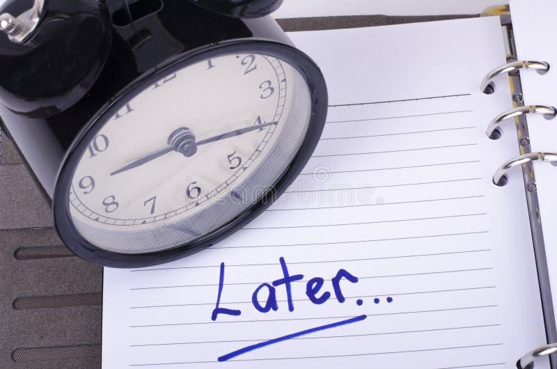 O conceito da procrastinação e da urgência com escrita exprime mais tarde o livro branco fotos de stock