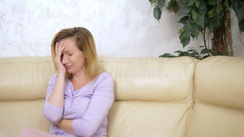 o conceito das emo??es assento de grito da mulher triste só no sofá na sala de visitas imagem de stock royalty free