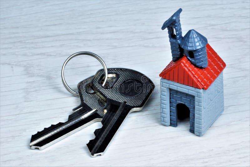 O conceito de bens imobiliários confortáveis - as chaves e a casa são um símbolo do bem estar Chave da casa em um fundo de madeir foto de stock
