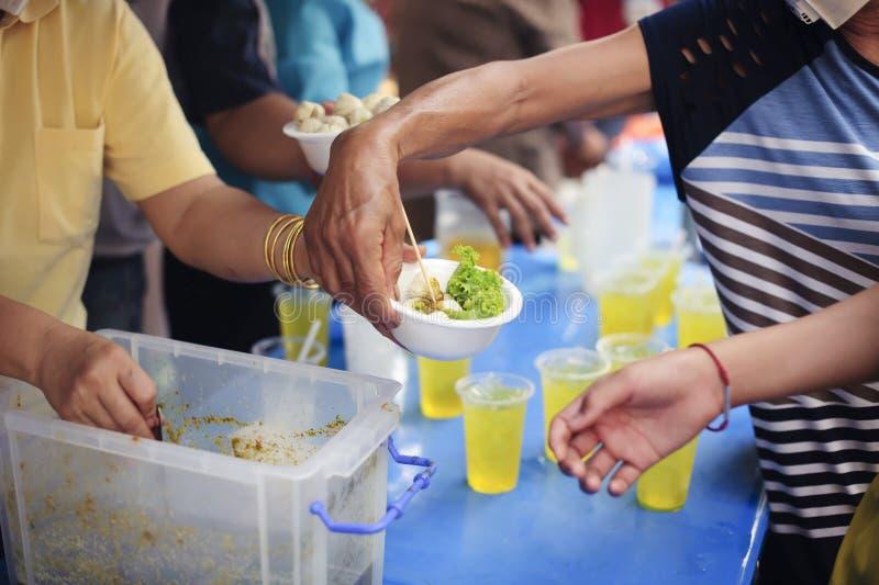 O conceito de compartilhar a ajuda: Participação em compartilhar o alimento para os pobres: O conceito do amor: O mendigo está es imagem de stock