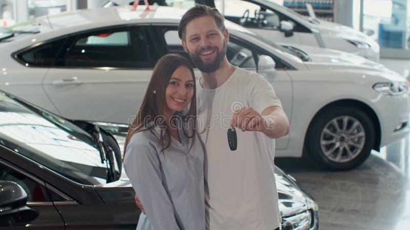 O conceito de comprar ou de alugar um carro Pares inter-raciais felizes novos com chaves novas do carro fotos de stock royalty free