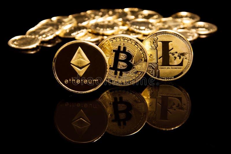 O conceito de Criptocurrency de moedas do litecion e do ethereum do bitcoin no espelho preto surge ao lado das moedas douradas foto de stock