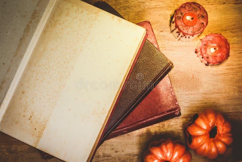 O conceito de Dia das Bruxas, livro velho abriu à página vazia e decorado com velas e abóboras imagem de stock royalty free