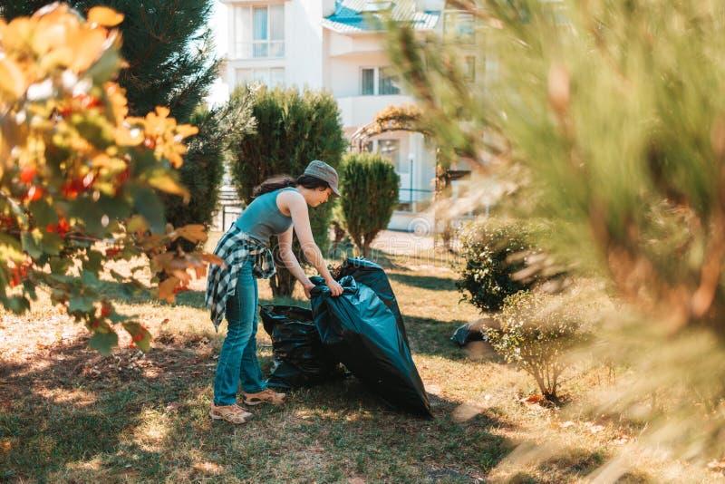 O conceito de poluição ambiental e o Dia da Terra Mulher voluntária fazendo limpeza no parque em frente à casa Ela... foto de stock
