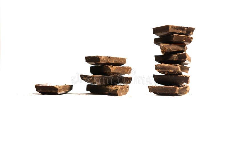 O conceito de um gráfico de lucro feito dos cubos do chocolate isolados no fundo branco com espaço da cópia imagem de stock
