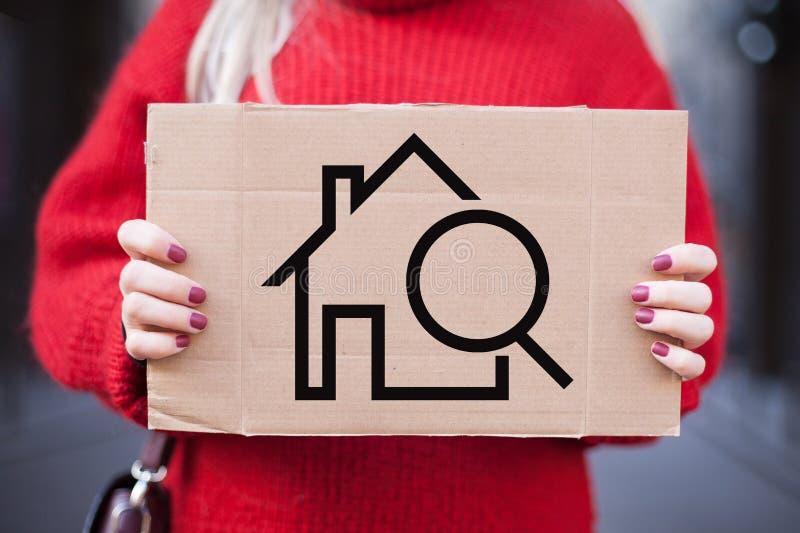 O conceito do aluguel, busca, compra de bens imobiliários Placa com a imagem de uma casa nas mãos de uma menina foto de stock