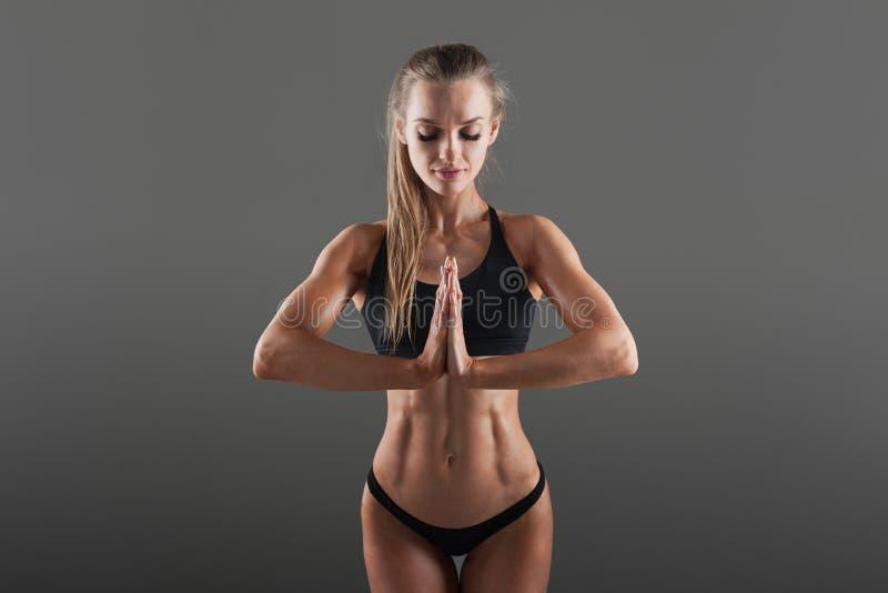 O conceito do autocontrole nos esportes Meditação antes do treinamento duro Uma menina bonita na roupa preta dos esportes foto de stock