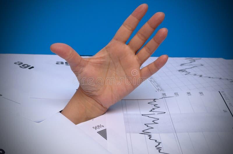 O conceito do auxílio com débitos do crédito Uma mão através dos papéis obtém a ajuda com a outra mão imagem de stock