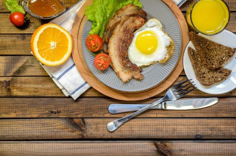O conceito do café da manhã inglês: ovo frito com bacon, suco de laranja e vegetais Espaço livre para o texto foto de stock royalty free