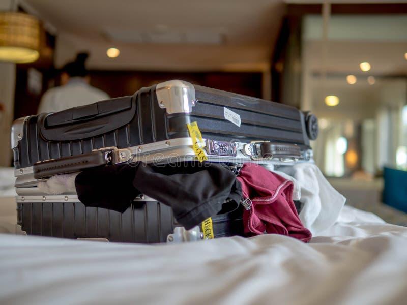O conceito do curso e das férias, embalando muitos roupa e material na mala de viagem na cama prepara-se para a viagem do curso e imagens de stock