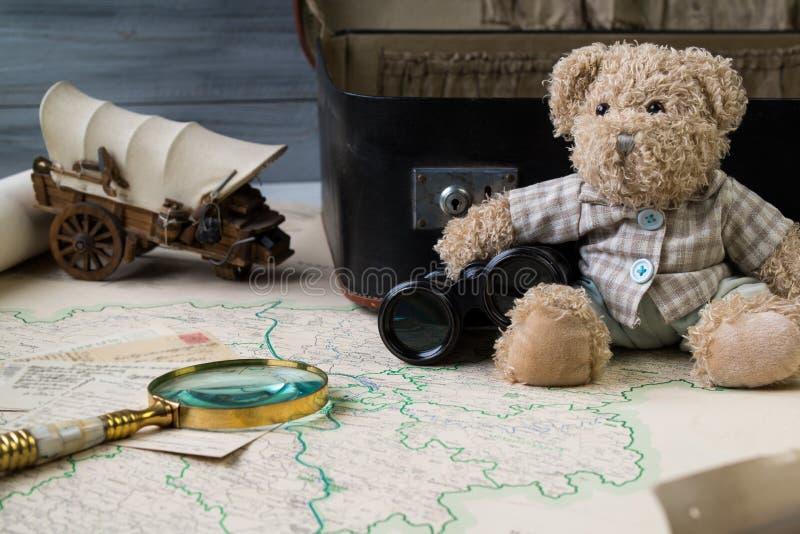 O conceito do curso, o urso de peluche com binóculos velhos e a mala de viagem no mapa antigo com ampliam o vidro imagem de stock royalty free