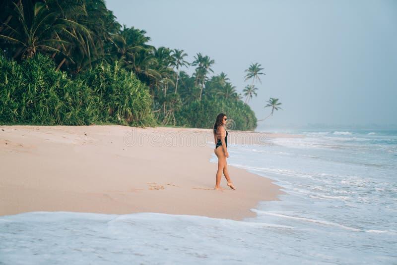 O conceito do curso, turismo, recreação no mar, pessoa Uma moça em um biquini dá uma volta ao longo da costa de um rosa imagens de stock