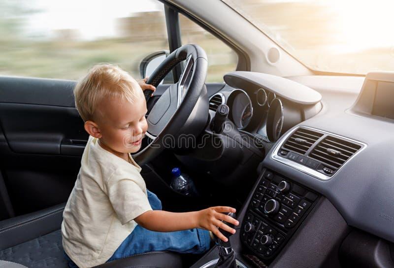 O conceito do desenvolvimento infantil adiantado, rapaz pequeno bonito está sentando-se na roda de um carro e conduz deftly um ca foto de stock royalty free