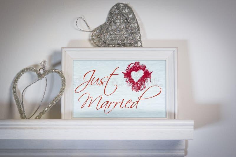 O conceito do dia do casamento com coração deu forma a ganchos e a quadro da foto sobre a prateleira branca imagem de stock