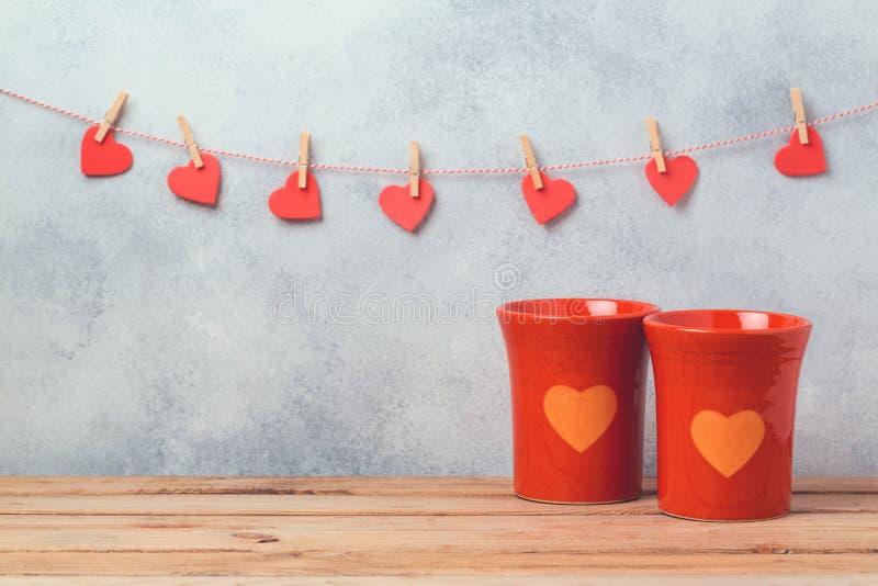 O conceito do dia de Valentim com copos e coração de café dá forma sobre o fundo com festão fotos de stock