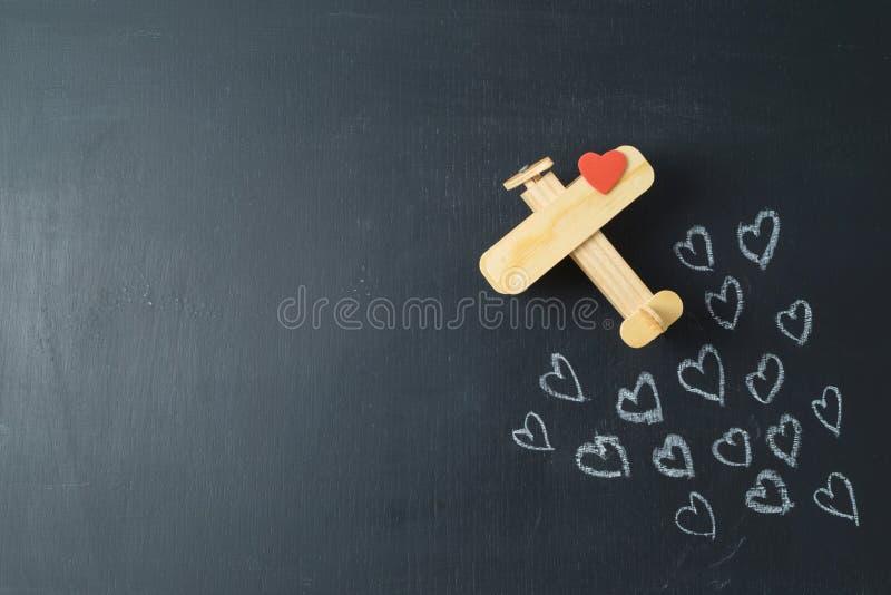 O conceito do dia de Valentim com formas do coração e o avião brincam sobre o fundo do quadro foto de stock royalty free