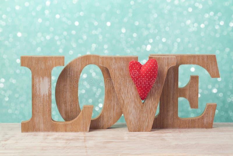 O conceito do dia do ` s do Valentim com letras de madeira amam e a forma do coração sobre o fundo do bokeh imagem de stock