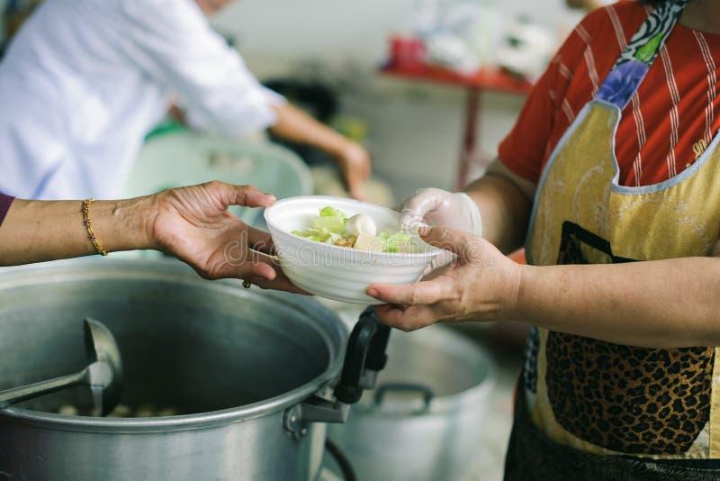 O conceito do humanitarismo: As mãos dos refugiados foram ajudadas pelo alimento da caridade para aliviar a fome: Conceitos de al imagem de stock