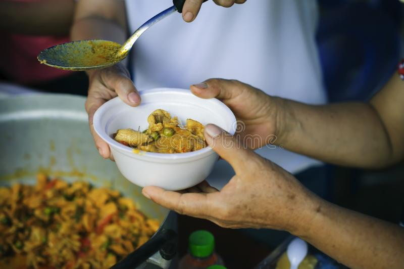 O conceito do humanitarismo: As mãos dos refugiados foram ajudadas pelo alimento da caridade para aliviar a fome: Conceitos de al fotografia de stock