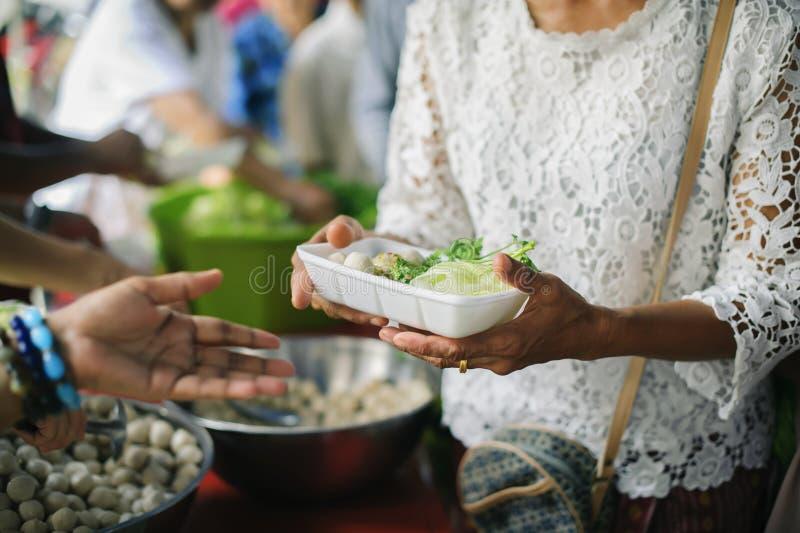O conceito do humanitarismo: As mãos dos refugiados foram ajudadas pelo alimento da caridade para aliviar a fome: Conceitos de al fotografia de stock royalty free