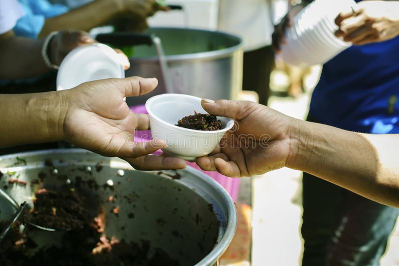 O conceito do humanitarismo: As mãos dos refugiados foram ajudadas pelo alimento da caridade para aliviar a fome: Conceitos de al imagem de stock royalty free