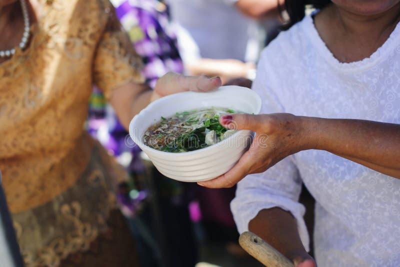 O conceito do humanitarismo: As mãos dos refugiados foram ajudadas pelo alimento da caridade para aliviar a fome: Conceitos de al fotos de stock royalty free