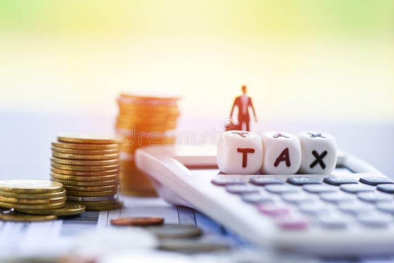 O conceito do imposto e a calculadora do homem de negócios das finanças empilharam moedas no papel da conta da fatura para o paga foto de stock royalty free