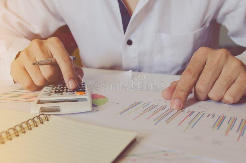 O conceito do negócio, fecha-se acima da mão do homem usando a calculadora e escrevendo faça a anotação com calcular no escritóri imagem de stock