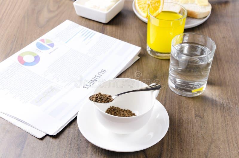 O conceito do negócio prepara breakfastQuickly o café, glasss da água, suco de laranja, jornal A manhã do homem de negócios fotografia de stock
