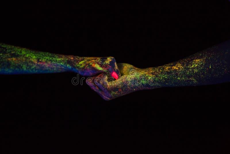 O conceito do tiro criativo de conexão das mãos nas palmas masculinas e fêmeas da luz de néon incandesce junto na obscuridade sob imagens de stock