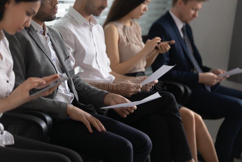 O conceito dos recursos humanos, executivos diversos dos candidatos senta-se na fileira foto de stock royalty free