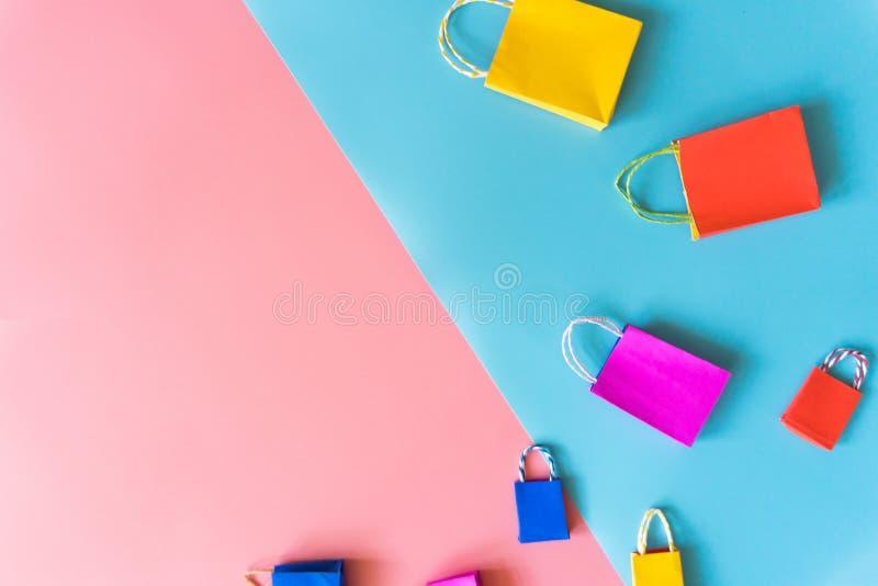 O conceito em linha da compra mínima, saco de compras de papel colorido vai para baixo de flutuar o fundo cor-de-rosa e azul para imagens de stock royalty free