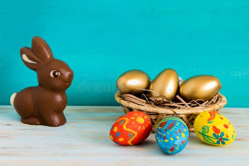 O conceito feliz da Páscoa com ouro do ANG da cor eggs na cesta ao lado do coelhinho da Páscoa do chocolate no fundo de madeira a fotos de stock royalty free