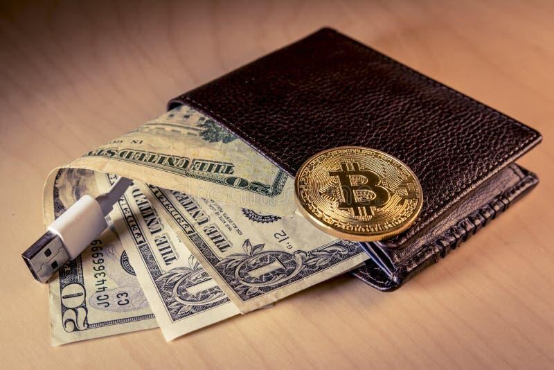 O conceito financeiro com Bitcoin dourado sobre uma carteira com dólares americanos e USB cabografam fotos de stock royalty free
