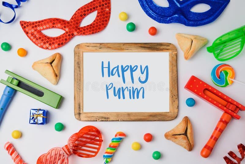 O conceito judaico de Purim do feriado com hamantaschen cookies, máscara do carnaval e quadro da foto no fundo branco fotos de stock