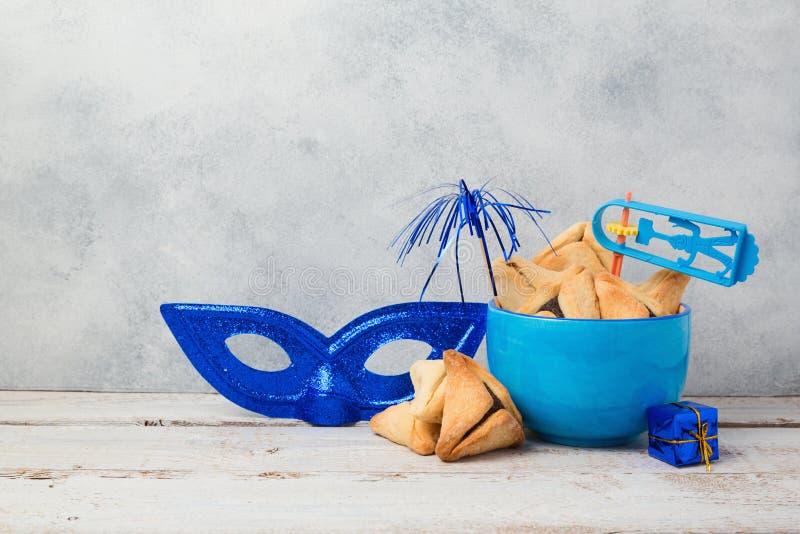 O conceito judaico de Purim do feriado com hamantaschen cookies ou orelhas dos hamans e máscara do carnaval imagem de stock